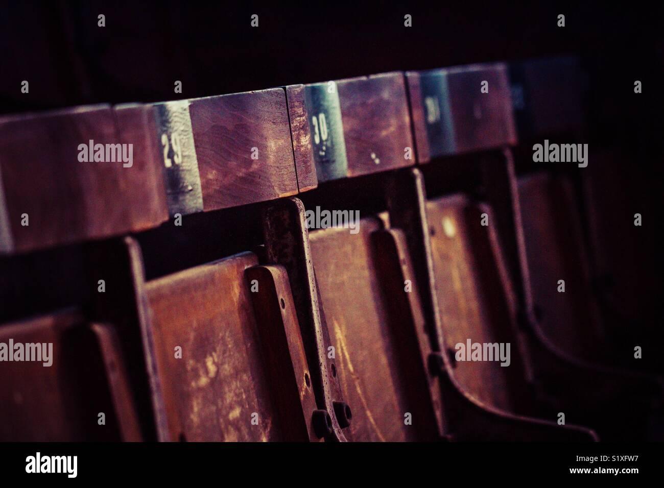 Una fila di dischi posti a sedere in legno con numeri in corrispondenza di un vuoto allo stadio di calcio di notte Immagini Stock