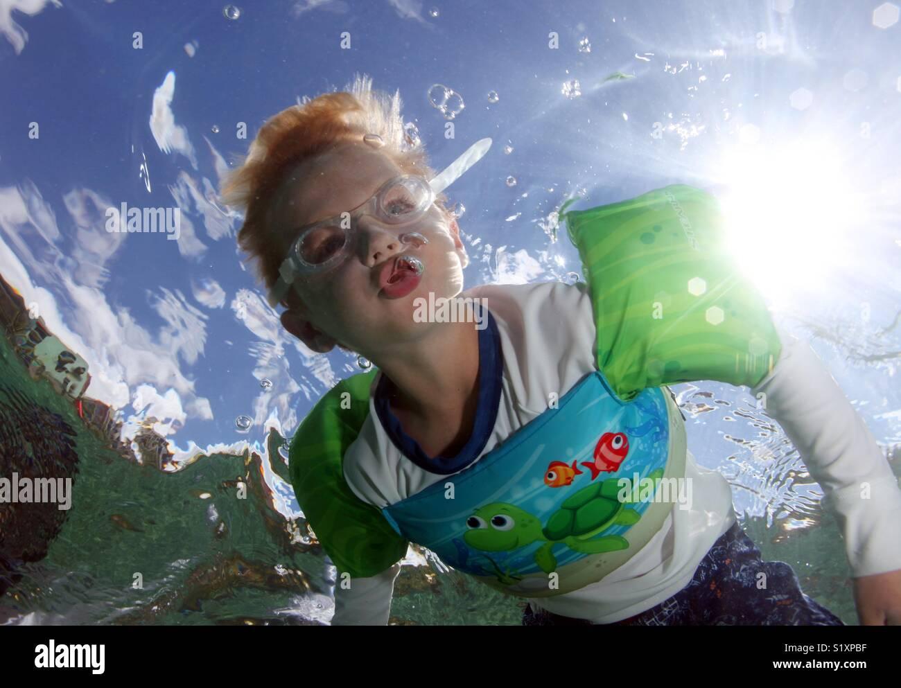 Un giovane ragazzo si brucia le bolle di aria mentre subacquee Snorkeling negli Stati Uniti Isole Vergini. Immagini Stock