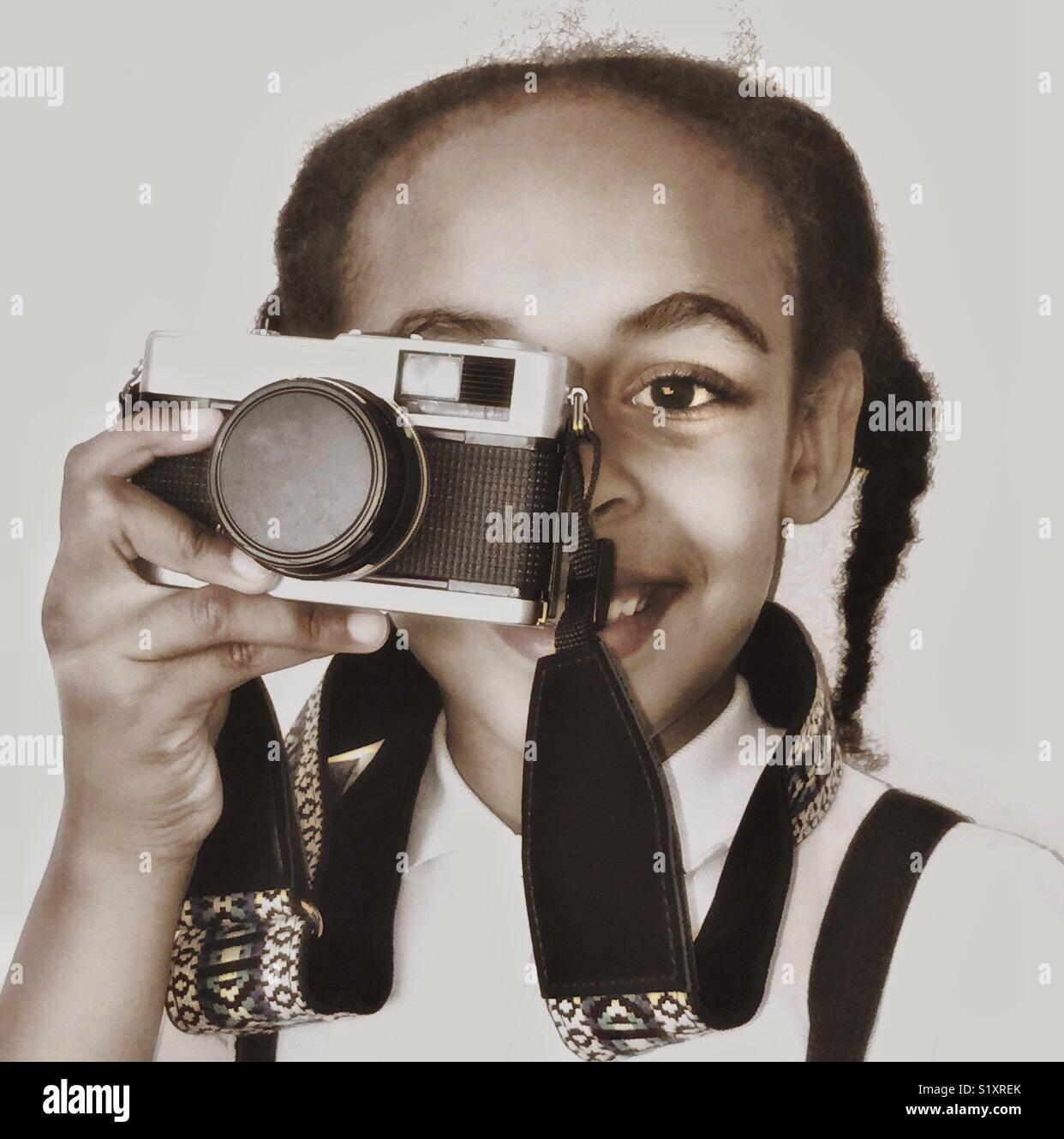 Una giovane ragazza con una fotocamera vintage al suo occhio. Immagini Stock
