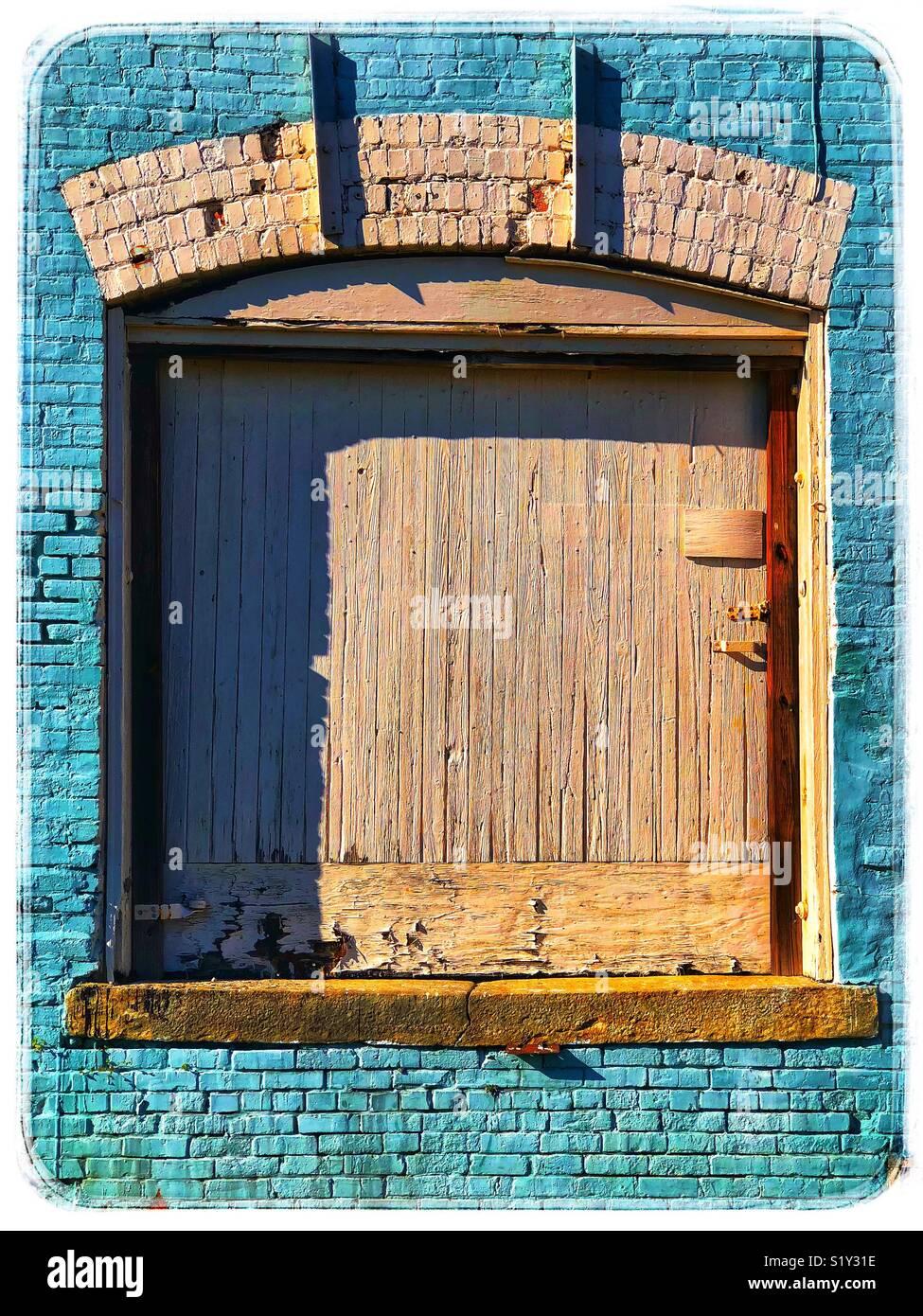 Il turchese muro di mattoni con la distressed porta in legno Immagini Stock