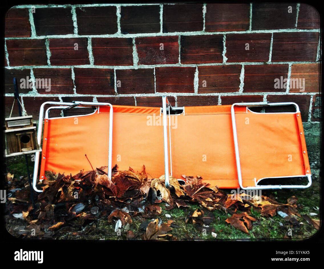 Prato arancione sedia appoggiata contro un muro di mattoni circondata da foglie di autunno. Immagini Stock
