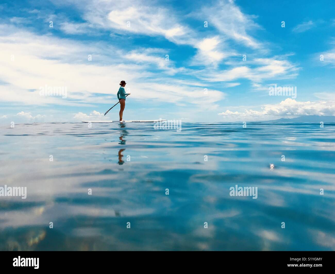 Una femmina di stand up paddling. Tavarua Fiji. Immagini Stock