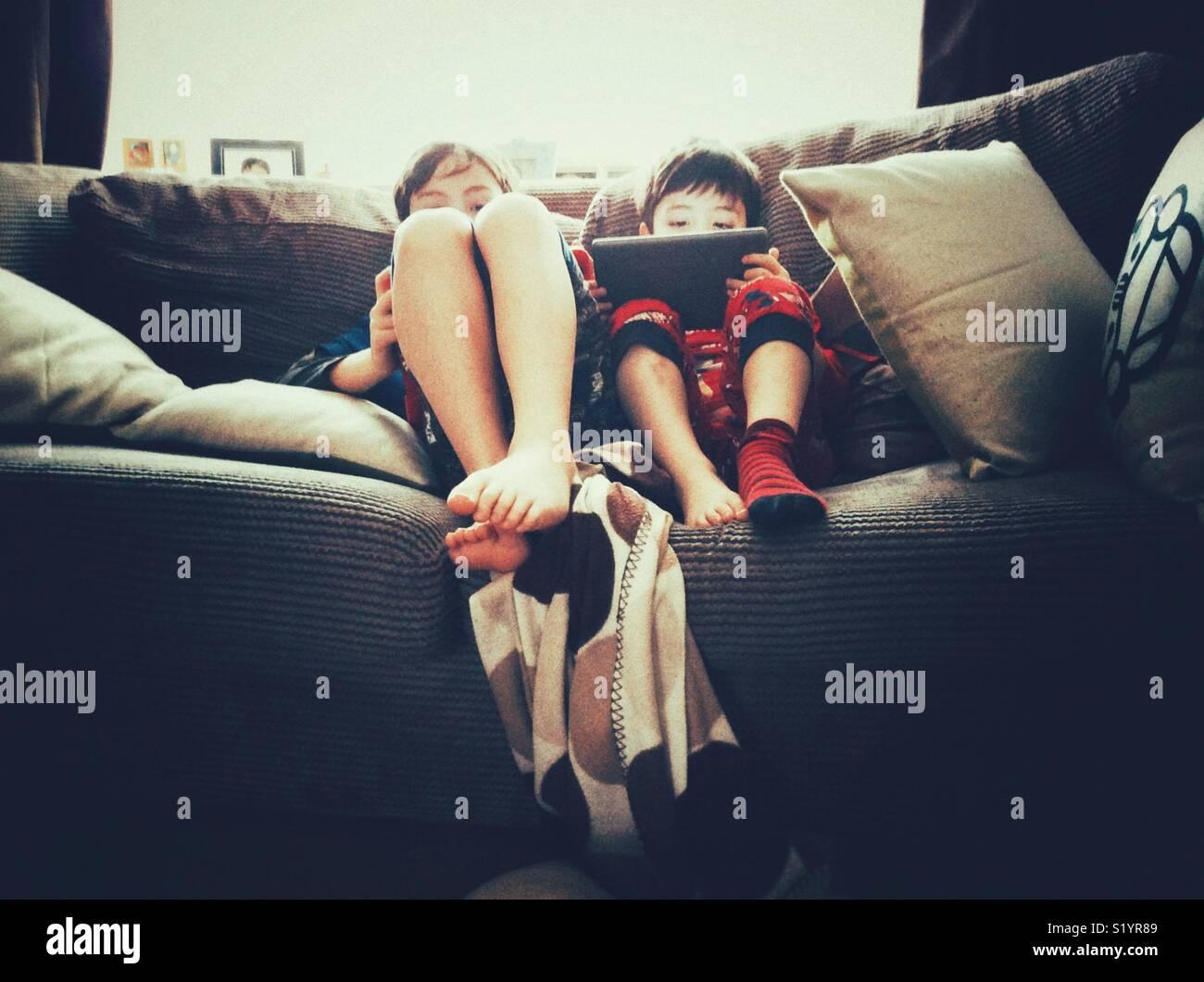 Due giovani fratelli seduti insieme su un divano giochi sul tablet PC. Immagini Stock