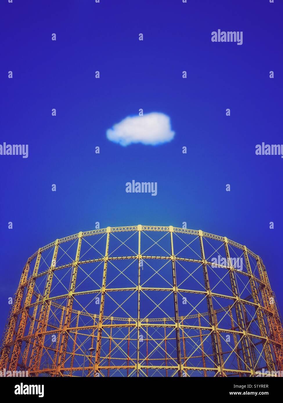 Struttura gasometro contro un vivido blu cielo con solitaria nube bianca Immagini Stock