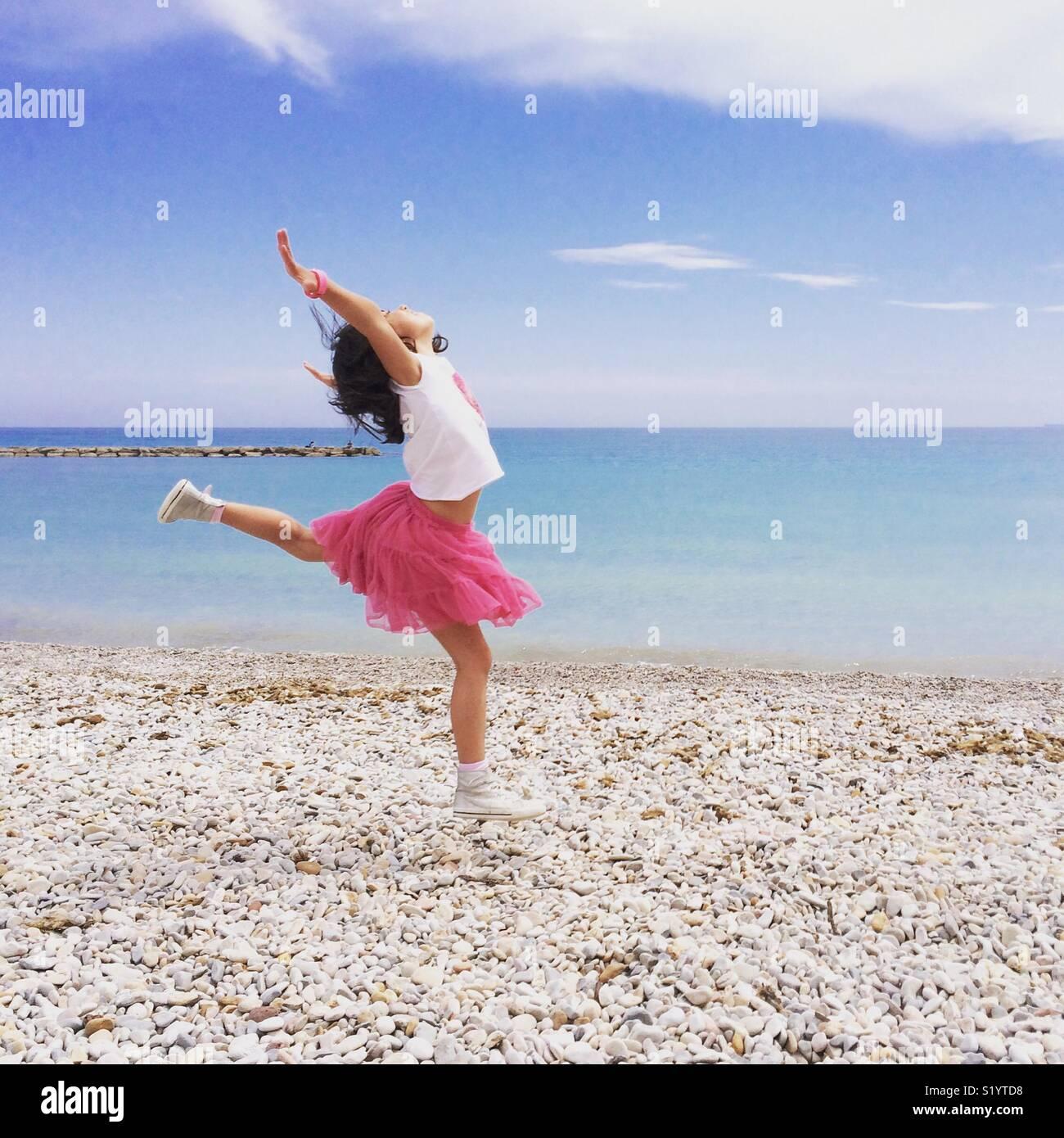Ragazza in gonna rosa dancing dalla riva del mare Mediterraneo Immagini Stock