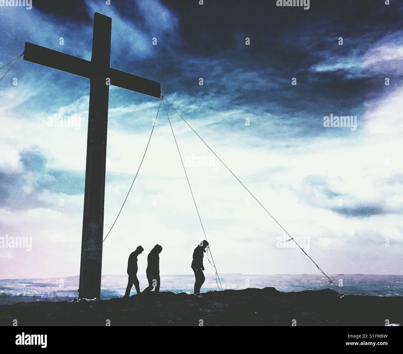 Silhouette di persone che sorgeva nei pressi di una grande croce di Pasqua Immagini Stock