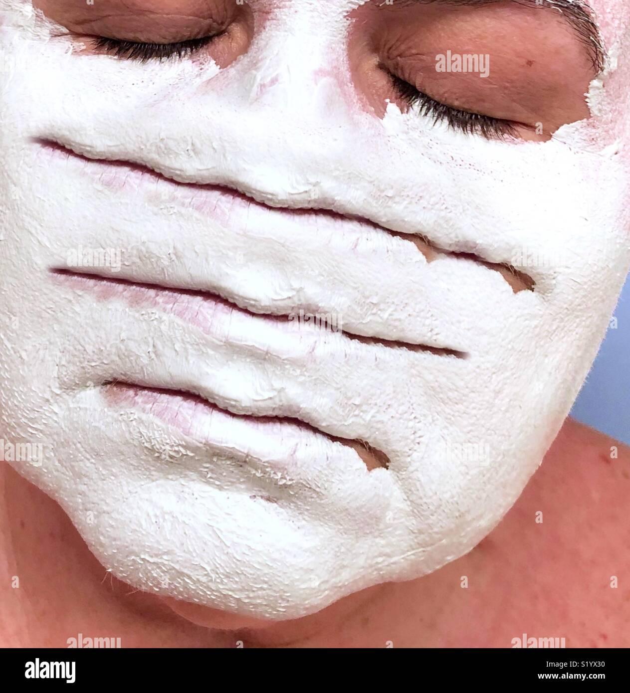 Un abstract illustrazione concettuale di una donna con gli occhi chiusi che indossa una argilla bianca maschera di fango con tre set di labbra Immagini Stock