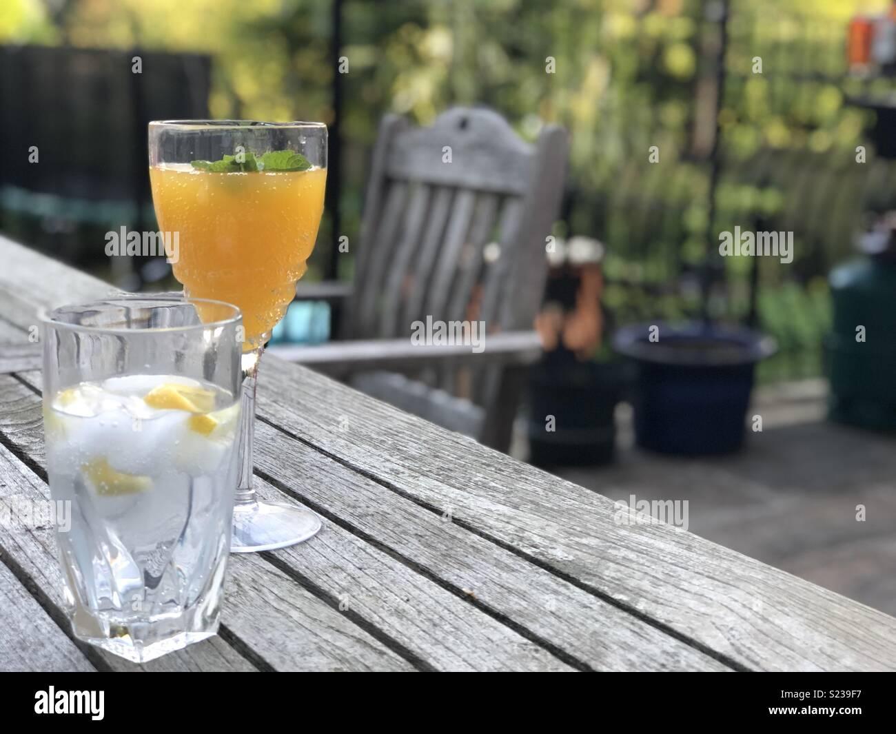Mamma e figlia bevande barbecue sulla terrazza del giardino - gin tonic e un mango e menta fizz. Immagini Stock