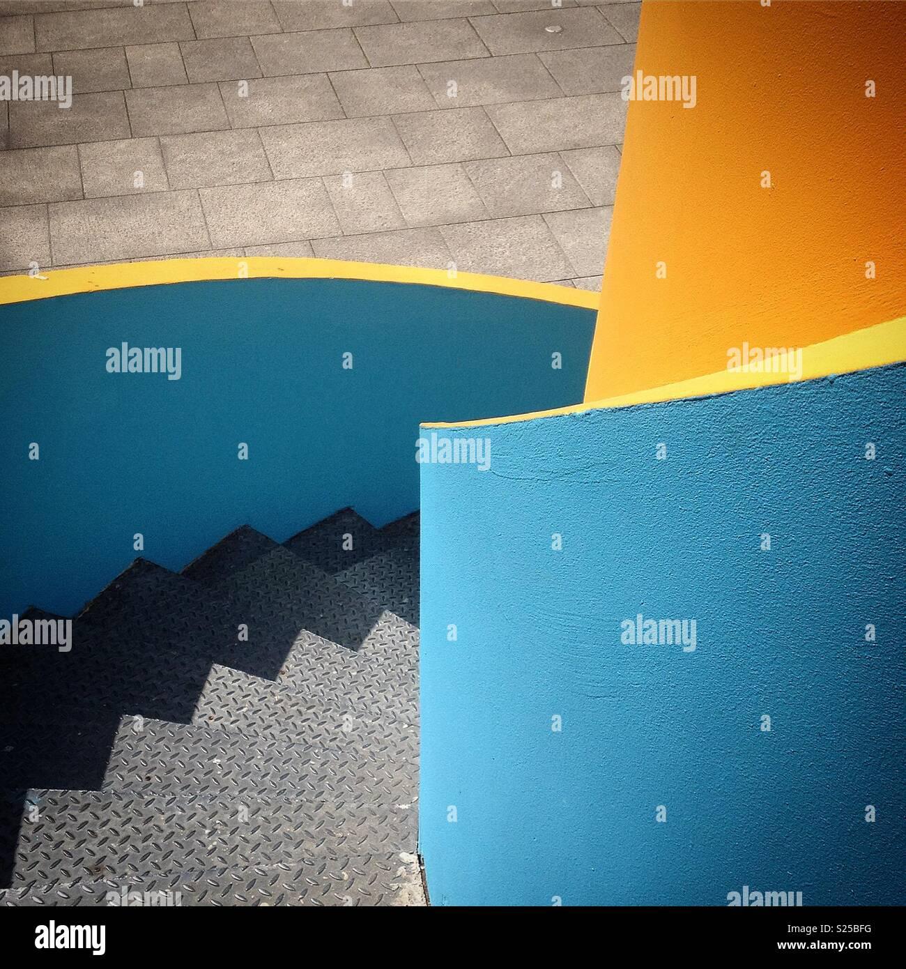 Gradini di metallo con il giallo e il blu dipinto di parete in calcestruzzo Immagini Stock