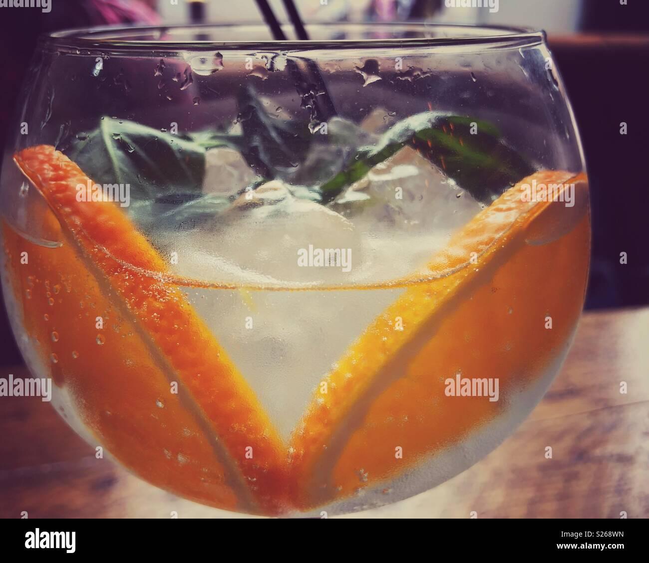 Gin Tonic con ghiaccio, fettine di arancia e le foglie di basilico. Immagini Stock