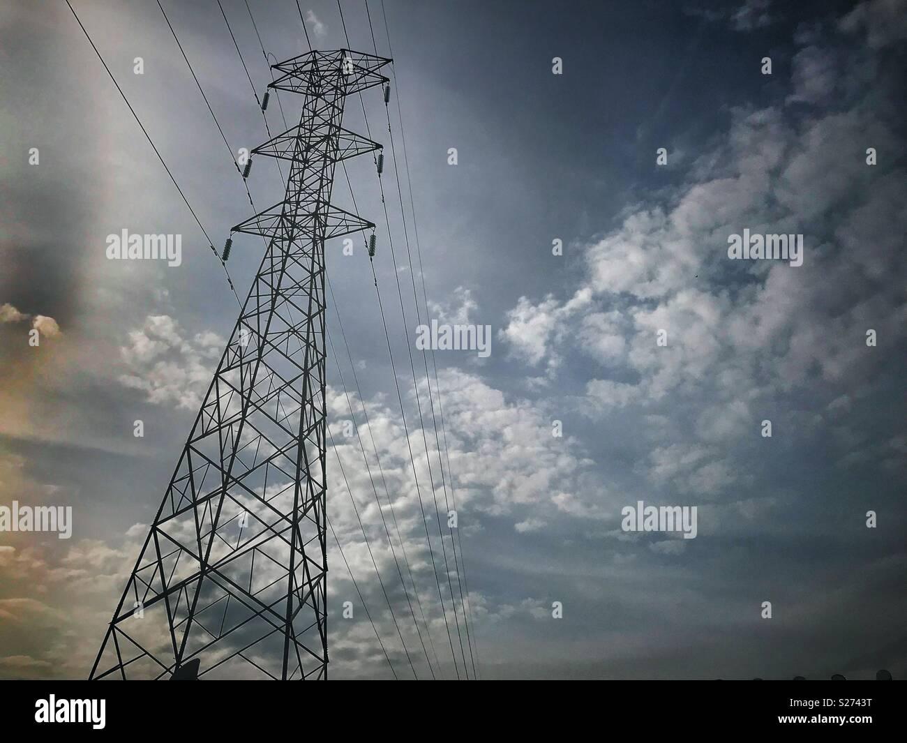 Torre de Electricidad en zona urbana y de fondo cielo nublado con contraste Immagini Stock