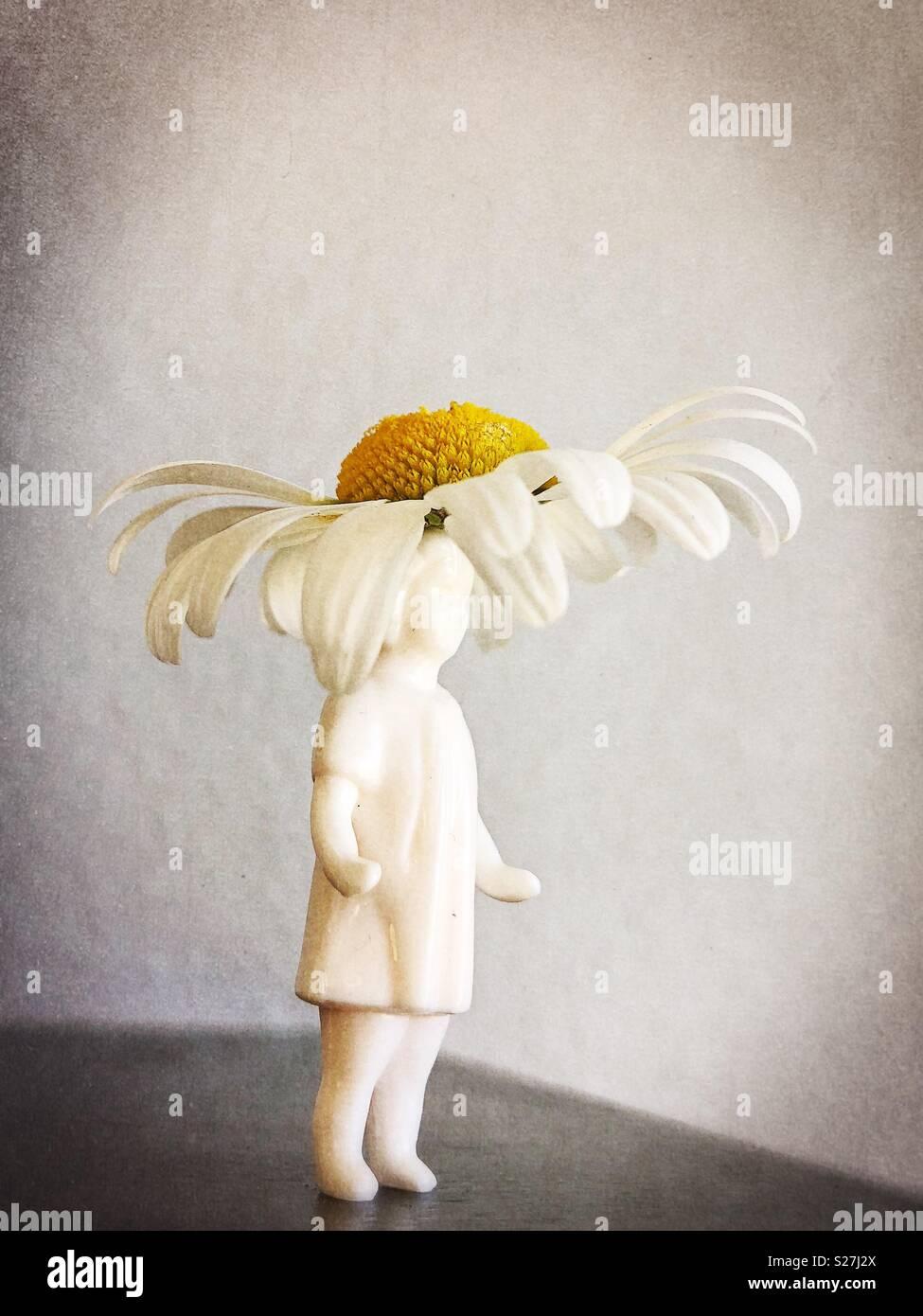 Figurina di una ragazza con daisy hat. Immagini Stock