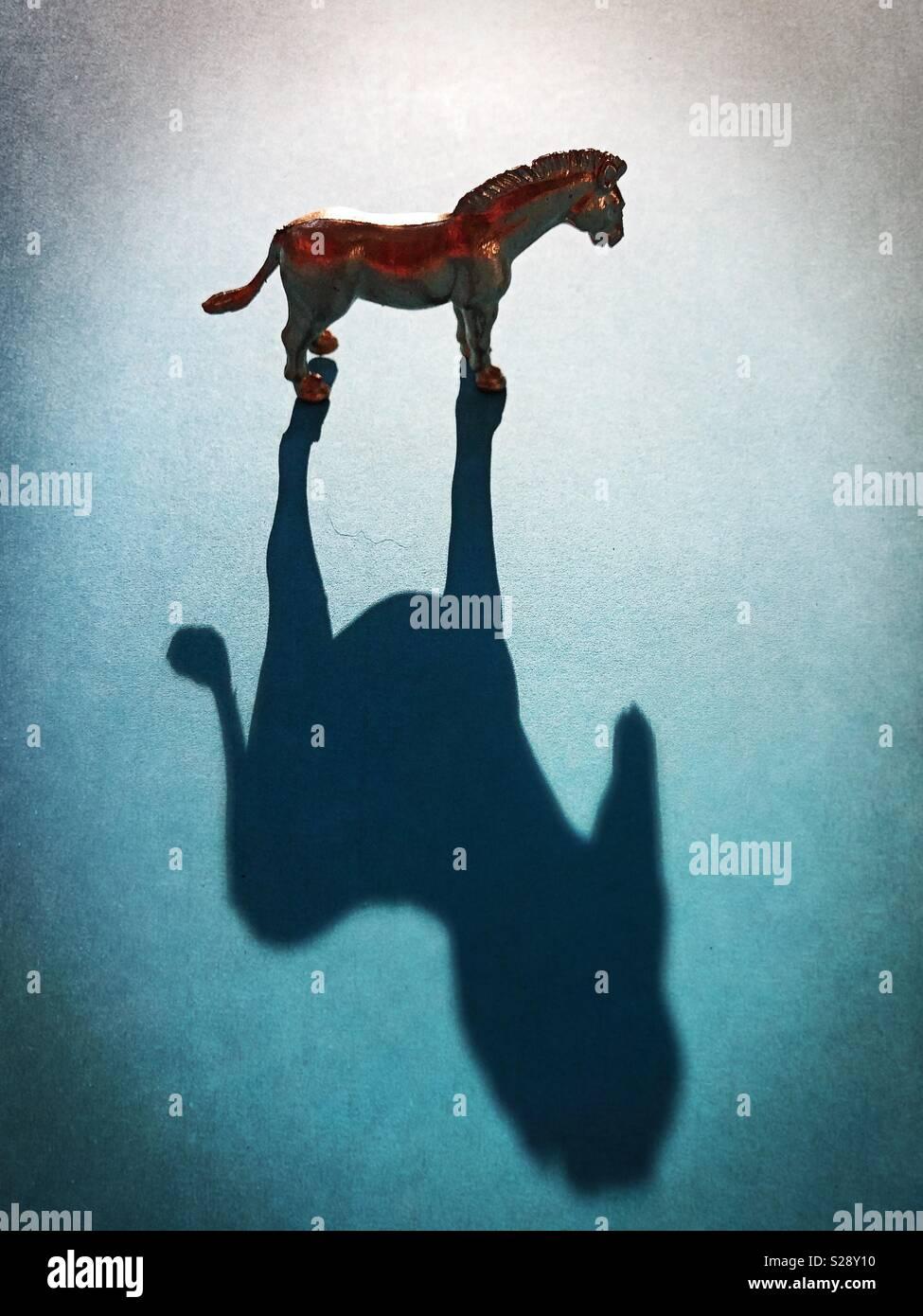 Un cavallo in oro e figurine di ombra. Immagini Stock