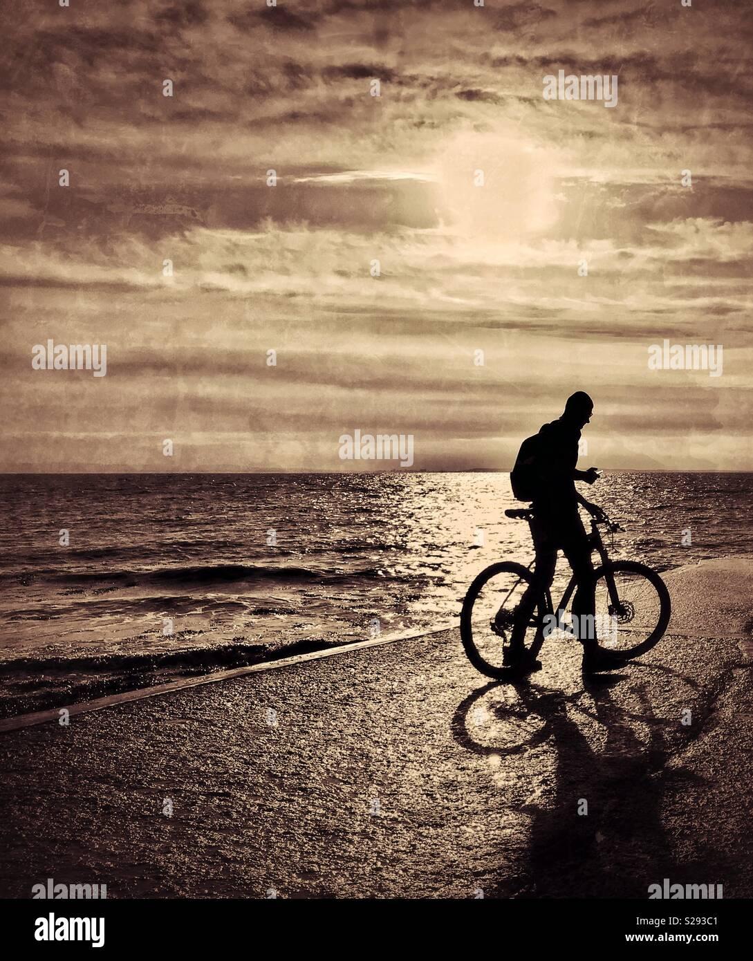 Un ciclista solitario controlla la sua mano dispositivo elettronico accanto al bordo delle acque al tramonto. Un immagine atmosferica con molteplici usi potenziali. Credito foto - © COLIN HOSKINS. Immagini Stock