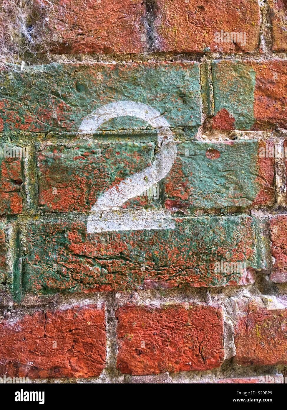 Il numero 2 nella vernice bianca su un muro di mattoni Immagini Stock
