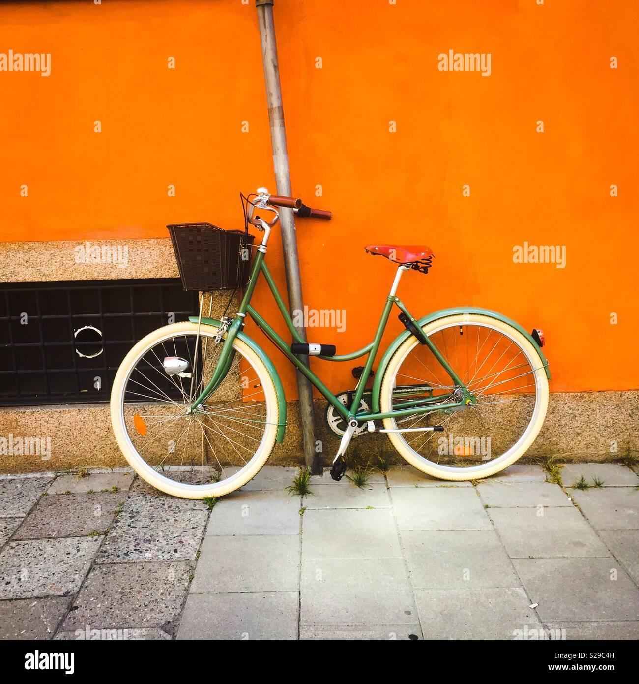 Bicicletta verde appoggiata contro la parete arancione Immagini Stock