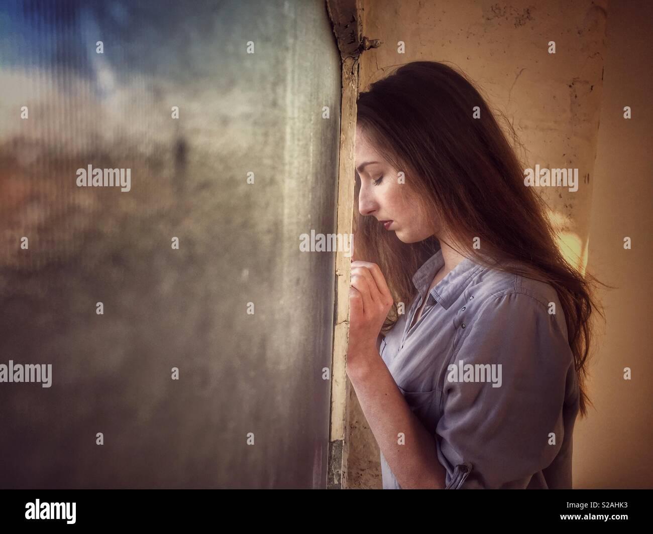 Triste donna appoggiata contro la finestra Immagini Stock