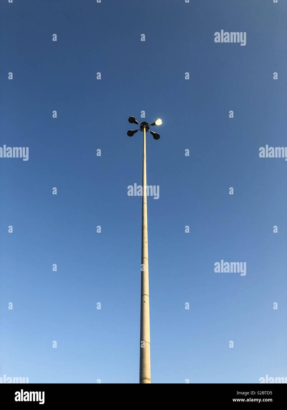 Il palo della luce con una sola luce di lavoro, contro un cielo blu chiaro. Immagini Stock