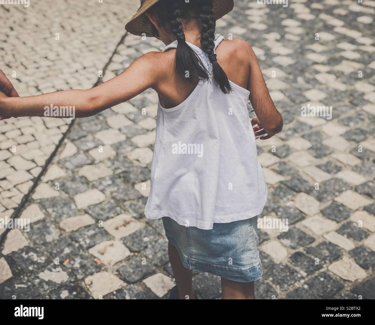 Ragazza con i capelli intrecciati e hat, camminando su una pietra piastrellato percorso, tenendo le mani adulte. Immagini Stock