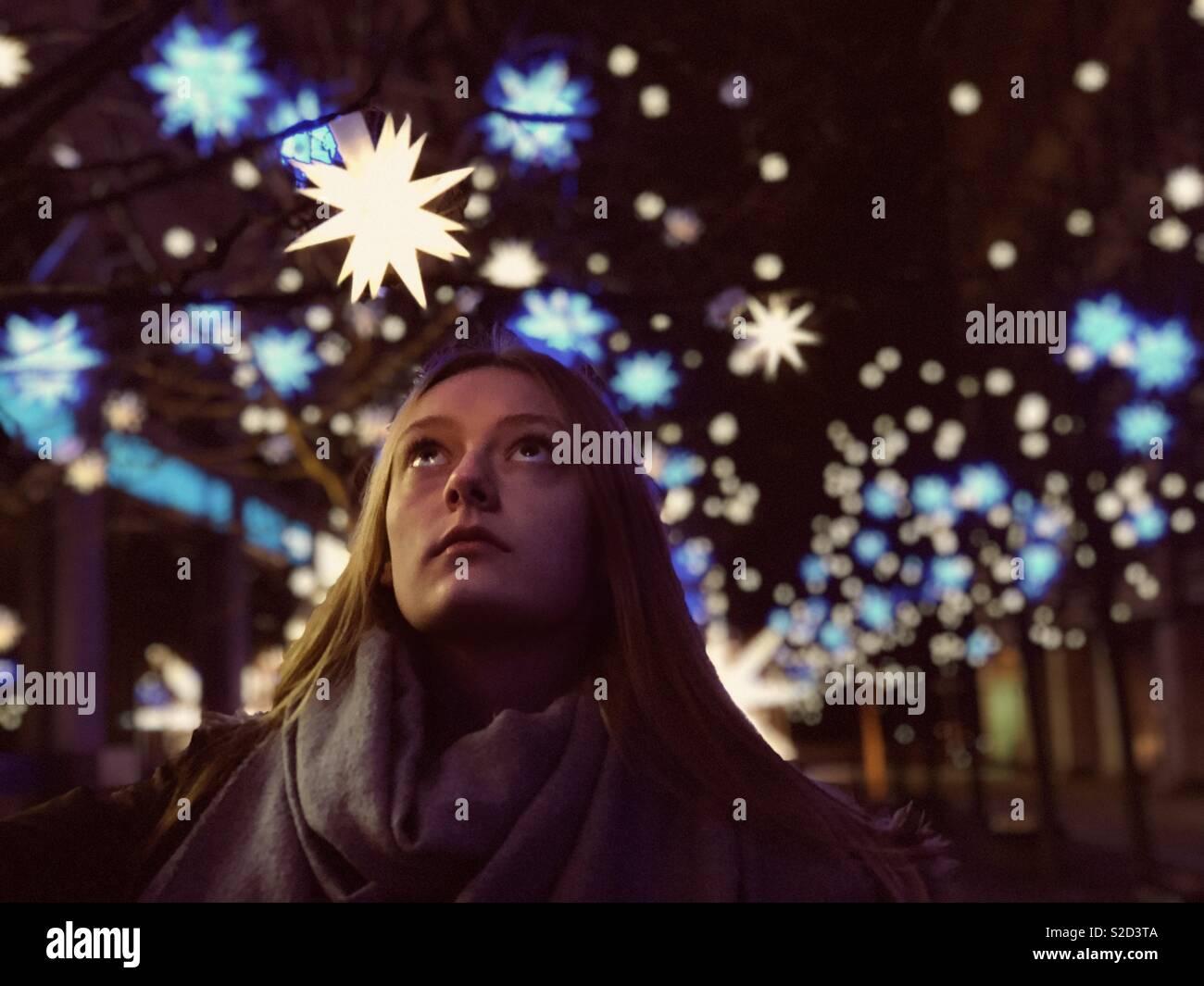 Giovane e bella donna che guarda fino a un lucente stella di natale decorazione. Immagini Stock