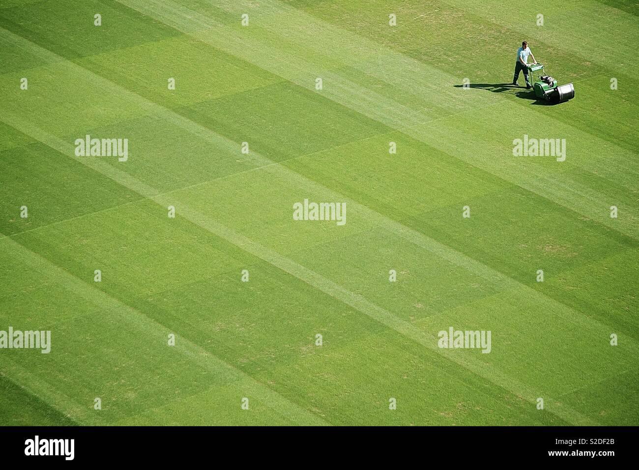 Un groundsman taglia l'erba. Immagini Stock