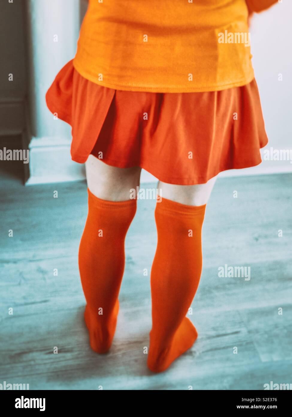 Cosplayer femminile come Velma. Indossare tutti orange Foto Stock