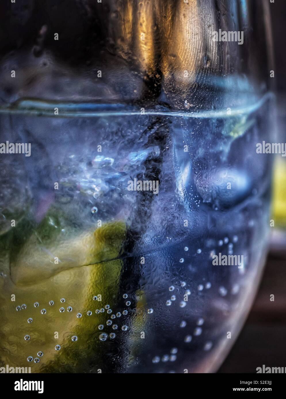 Gin Tonic. Lime. Paglia e impronte digitali. Immagini Stock
