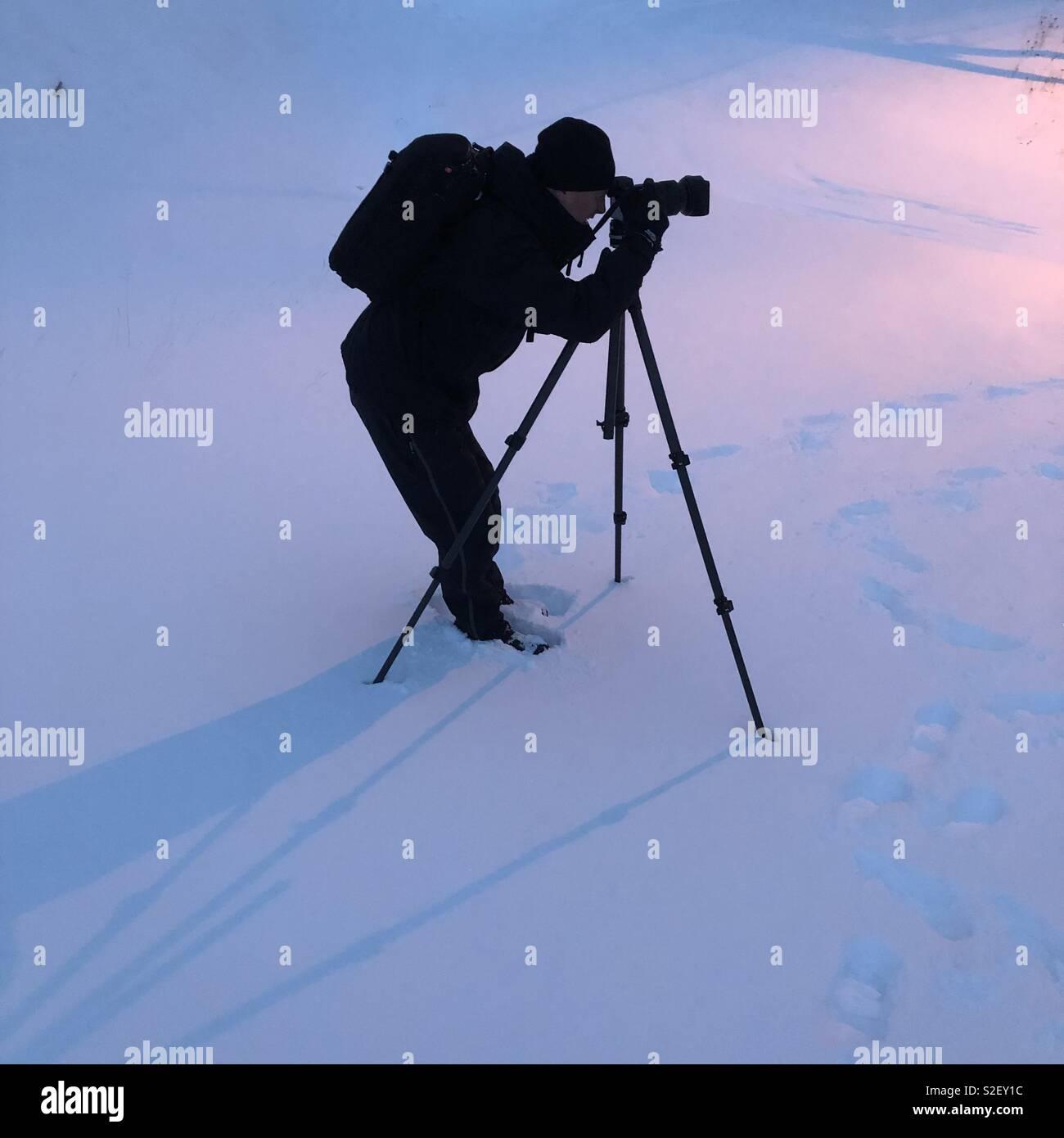 Fotografo maschio con treppiede nella neve profonda. Foto Stock