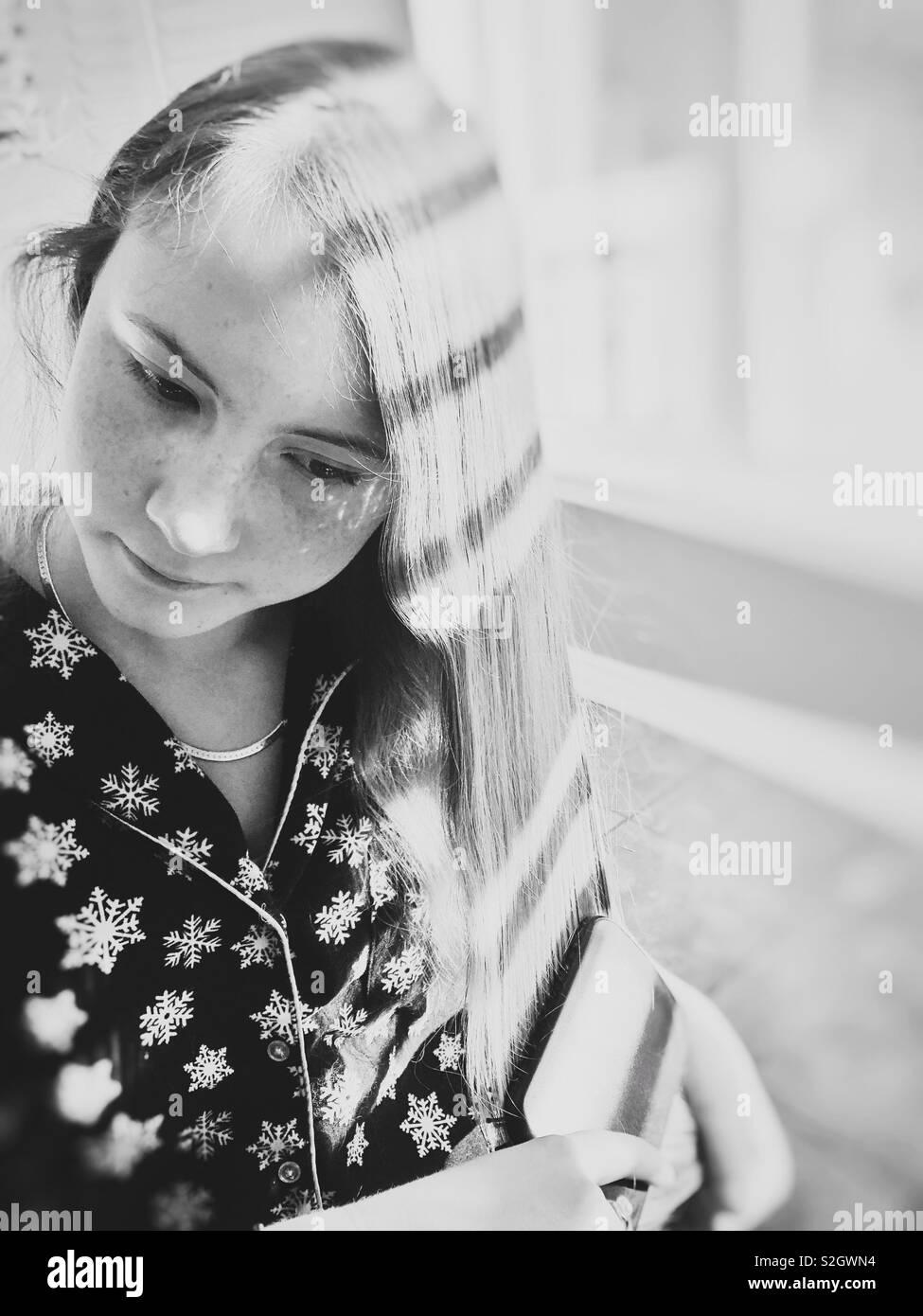 Ariosa immagine in bianco e nero della ragazza adolescente di spazzolatura, lunghi capelli biondi da una finestra con la luce del sole e ombre Foto Stock