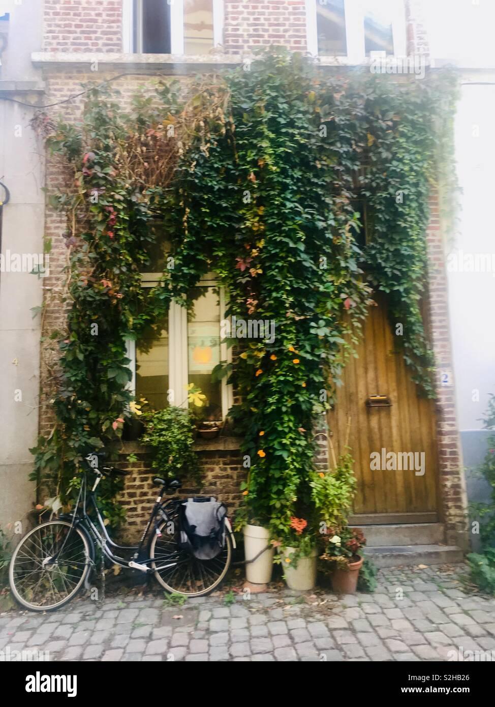Facciata romantica di casa con la bicicletta Foto Stock