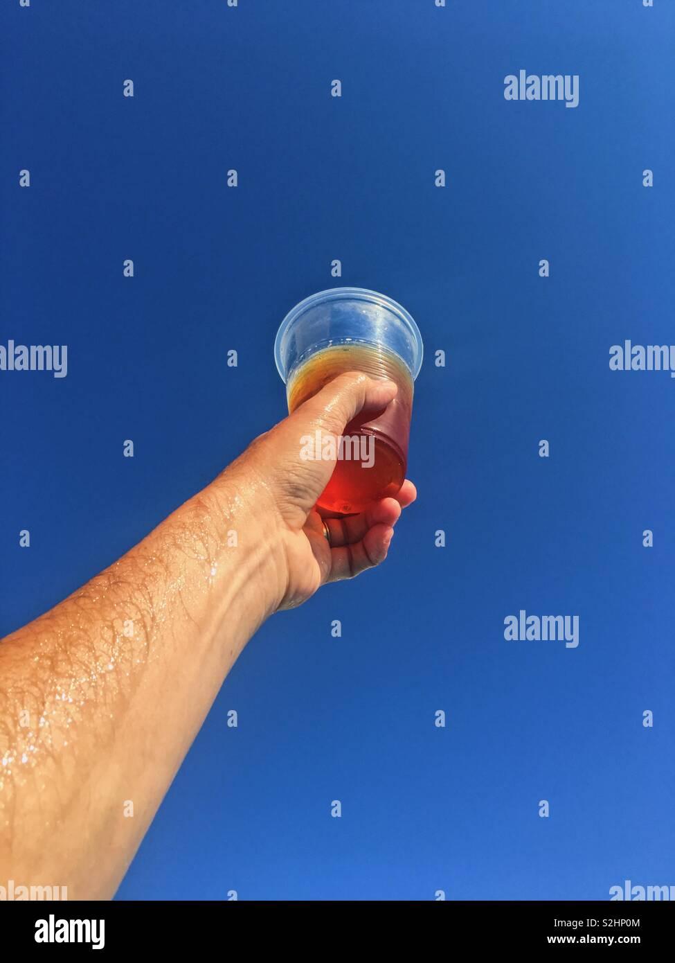 Sollevamento di un bicchiere di birra fino al blu intenso del cielo. Foto Stock