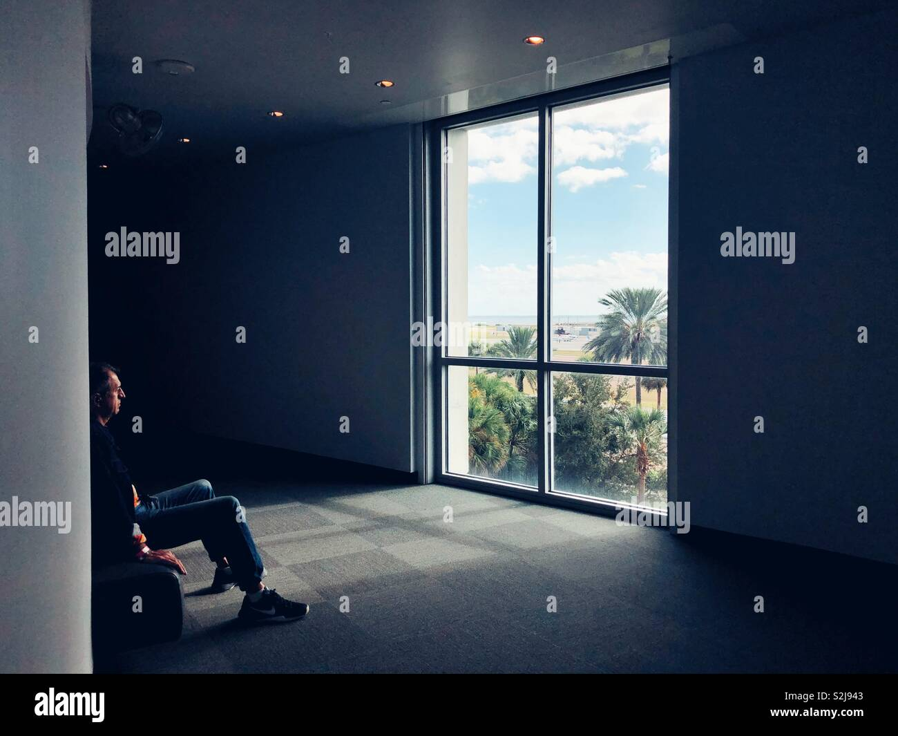 L'uomo ha perso in pensieri seduto in contemplazione stanza in Salvador Dali Museum di San Pietroburgo, Florida Foto Stock
