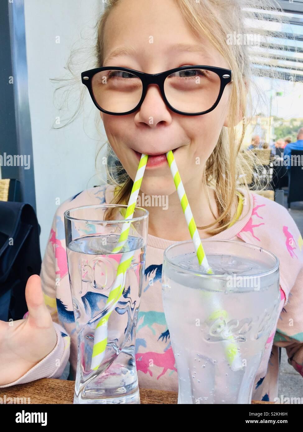 Bambino femmina bere due bicchieri con due cannucce Immagini Stock