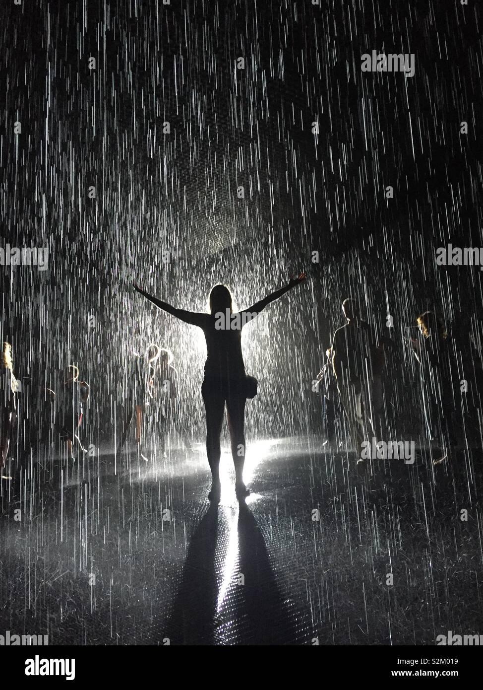 Donna in piedi nella camera di pioggia Immagini Stock
