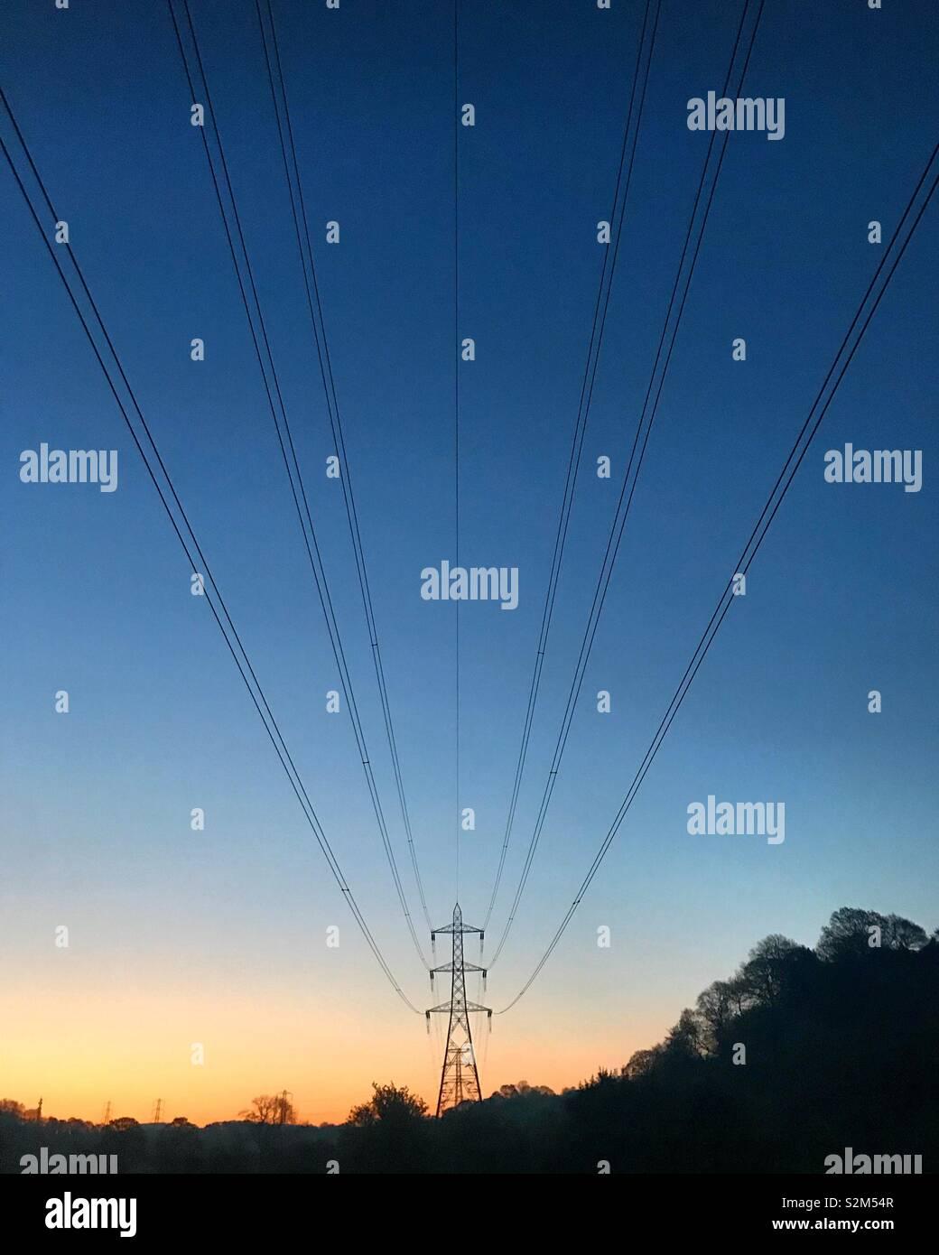 Le linee di alimentazione contro un sunrise a Manchester in Inghilterra Foto Stock