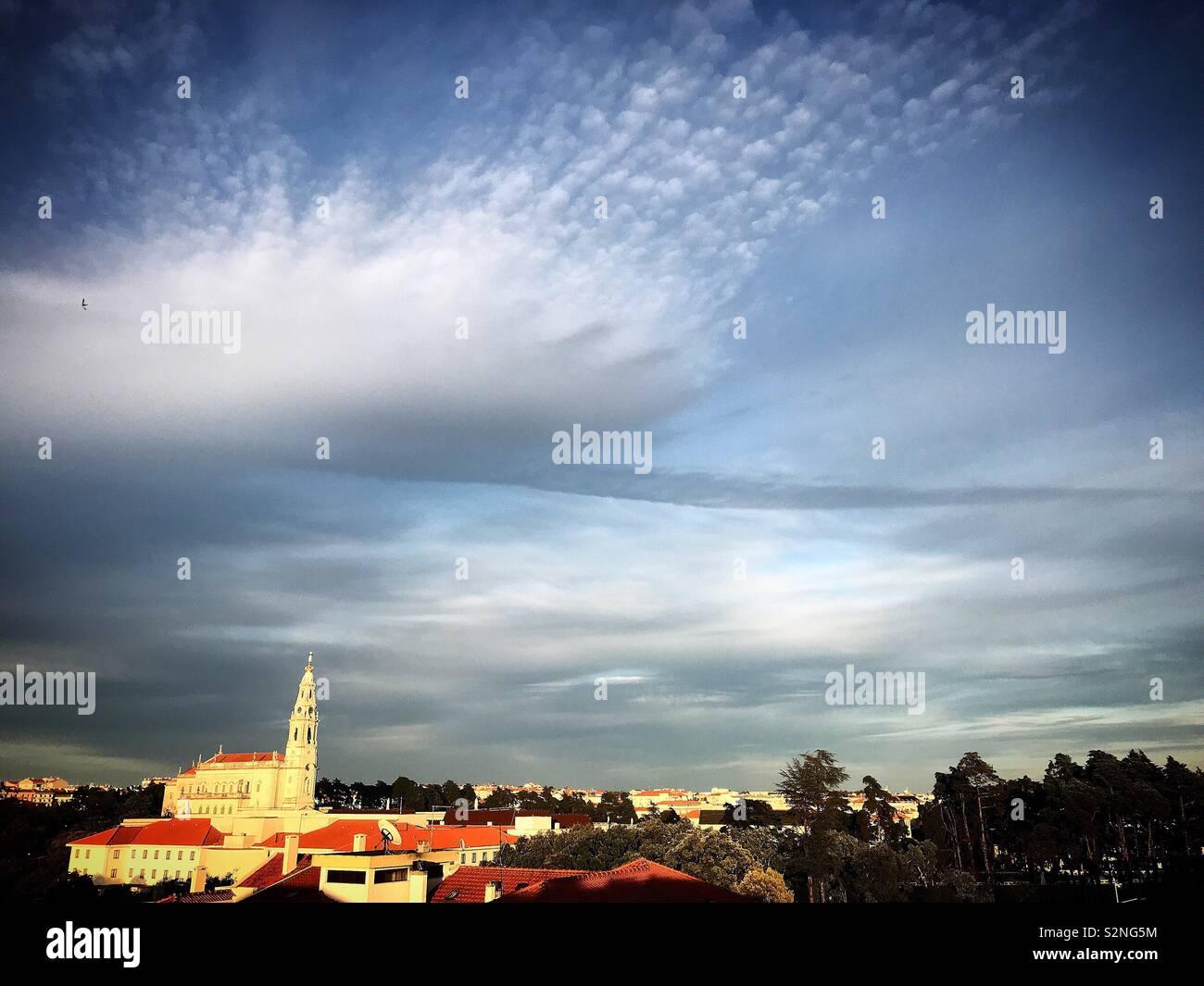 Una nuvola con la forma di una nuvola e una linea nera formata dal fumo da una pianura oltre la Nostra Signora del Rosario sactuary a Fatima, Portogallo Foto Stock