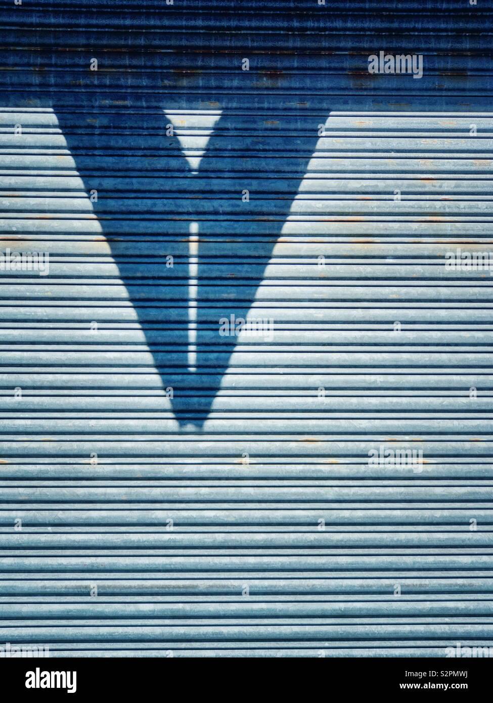 Ombra su una grande porta di metallo. Foto Stock