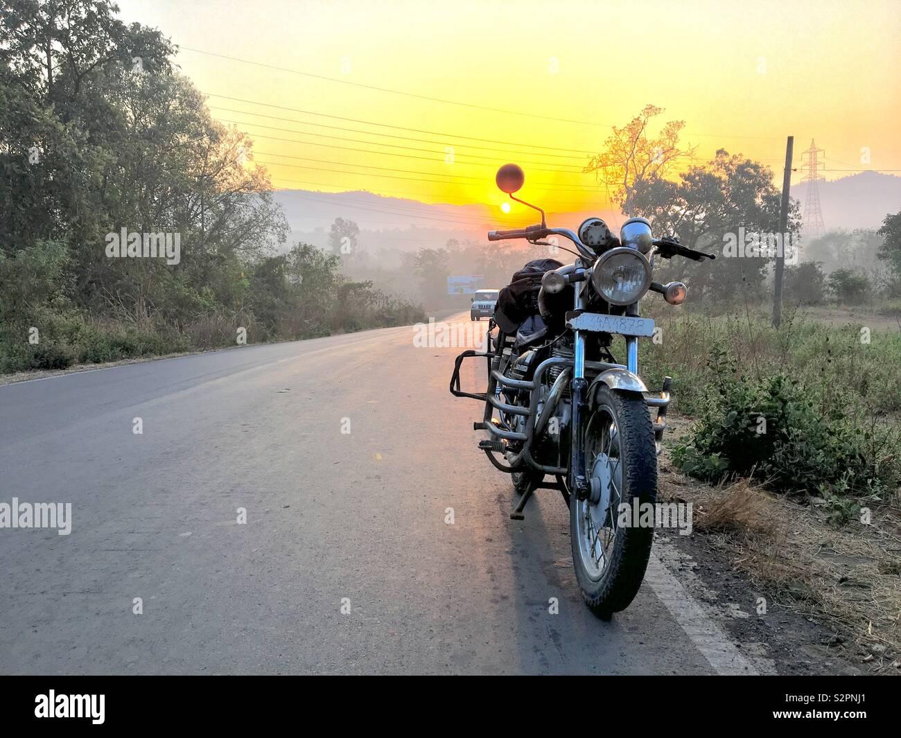 Inquadratura di un pranzo motociclo su una strada di sunrise Foto Stock