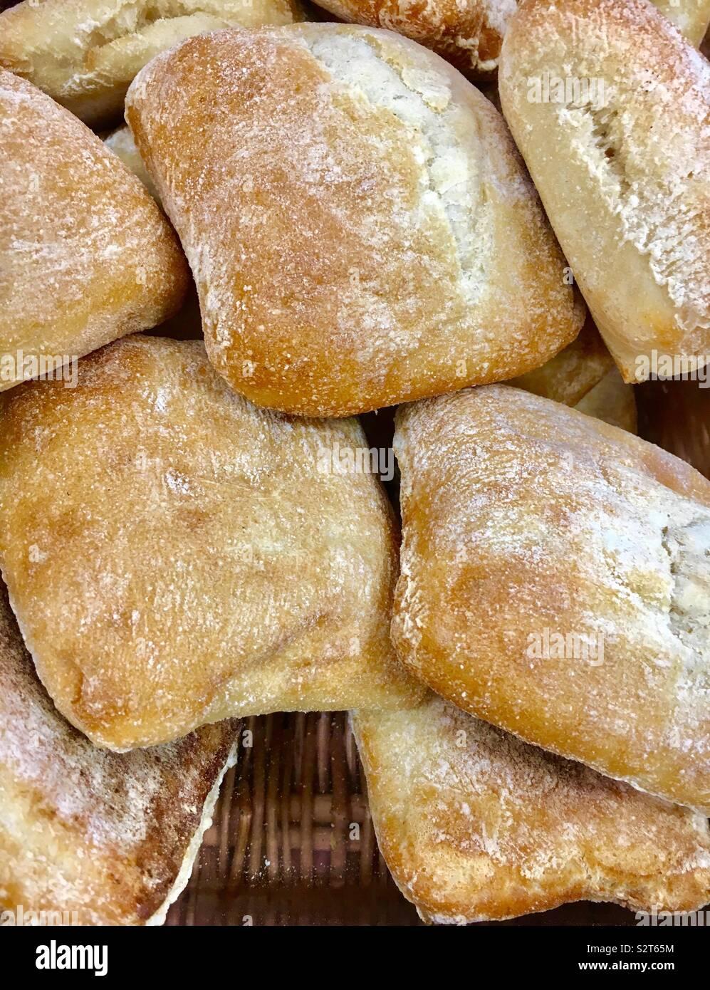 Cesto pieno di pane appena sfornato ciabatta pane in vendita presso un panificio Foto Stock