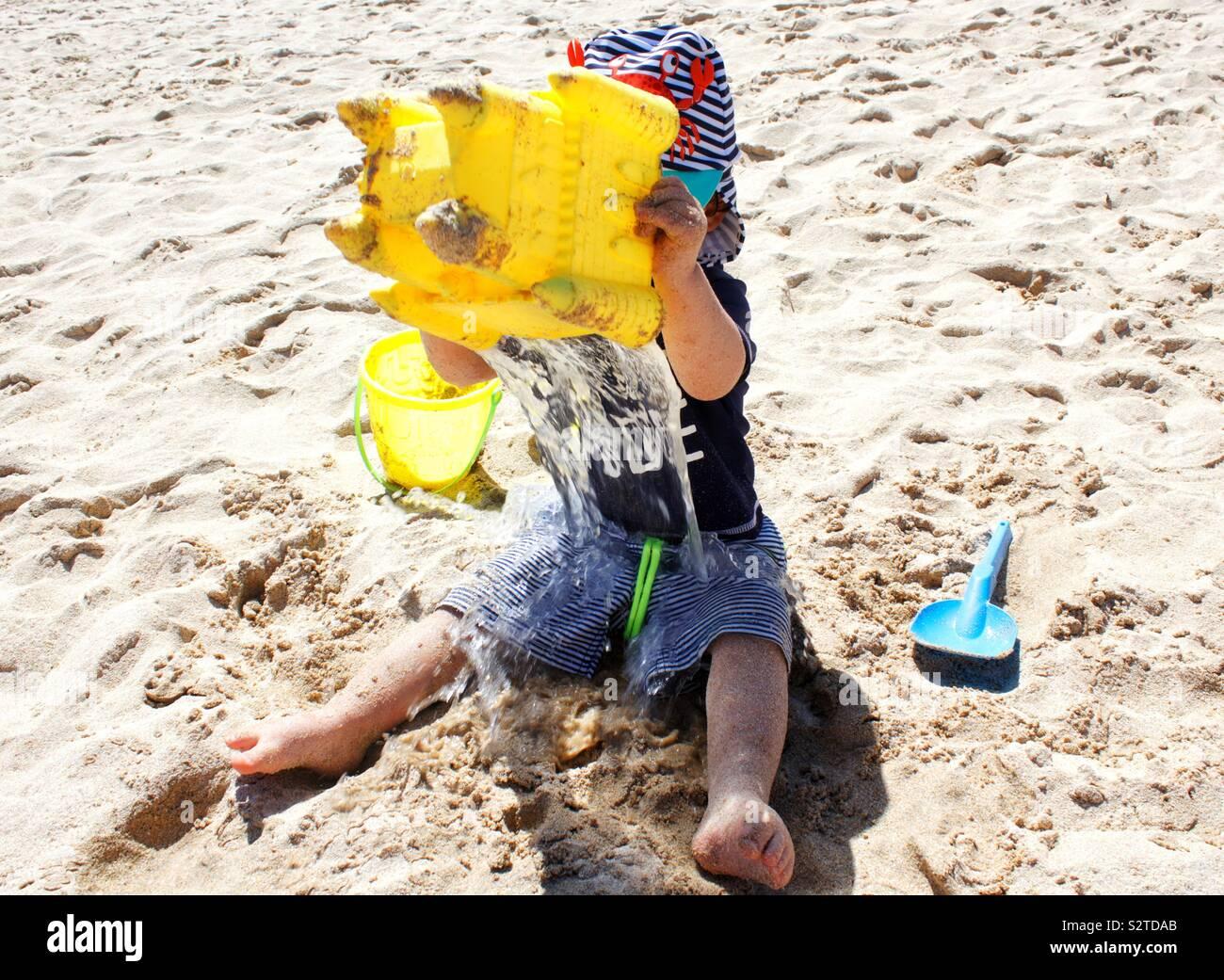 Il Toddler versando un secchio di acqua su se stesso Foto Stock
