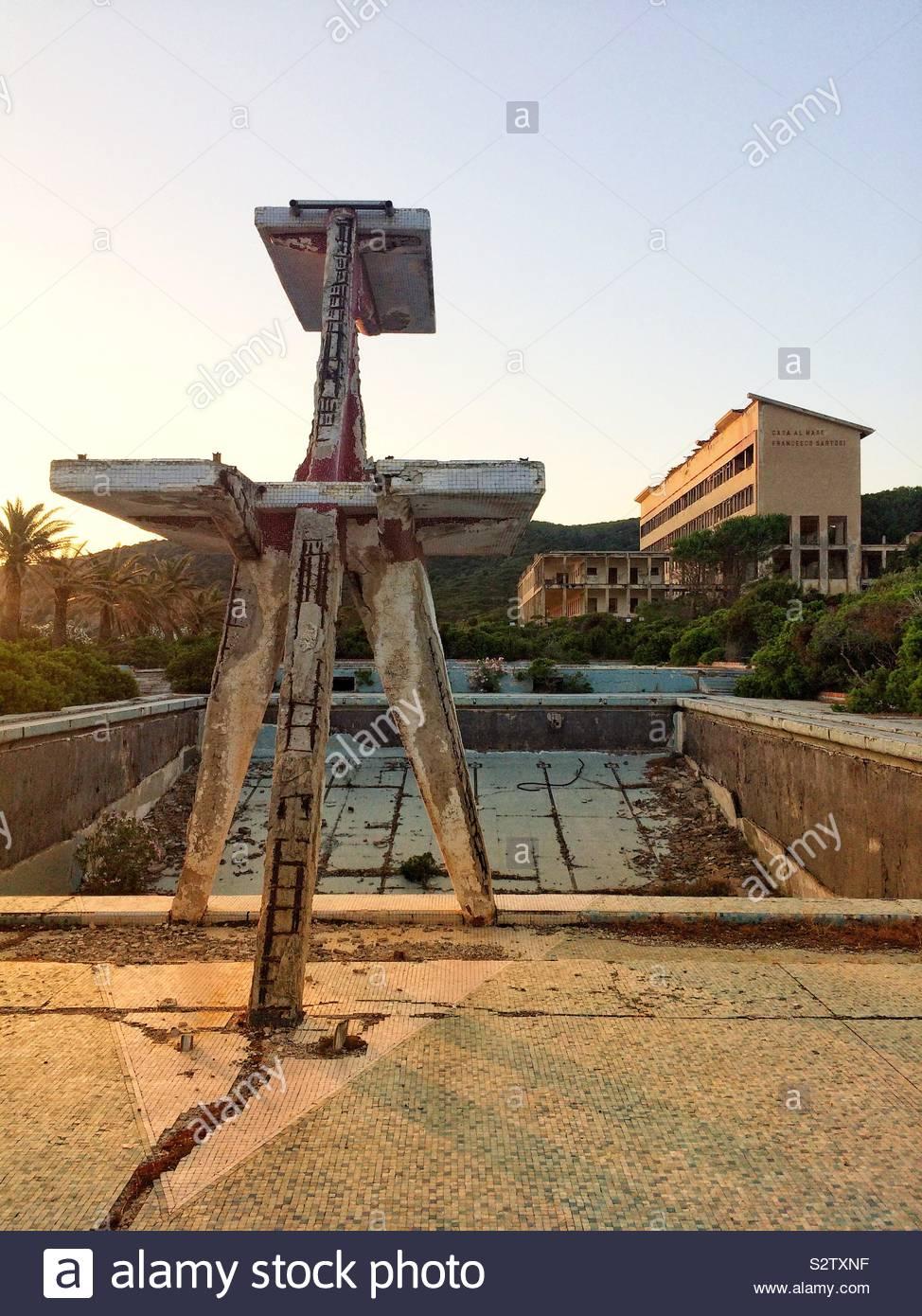 Un hotel abbandonato e svuotare la piscina con trampolino che assomiglia a un stalking dinosauro Foto Stock