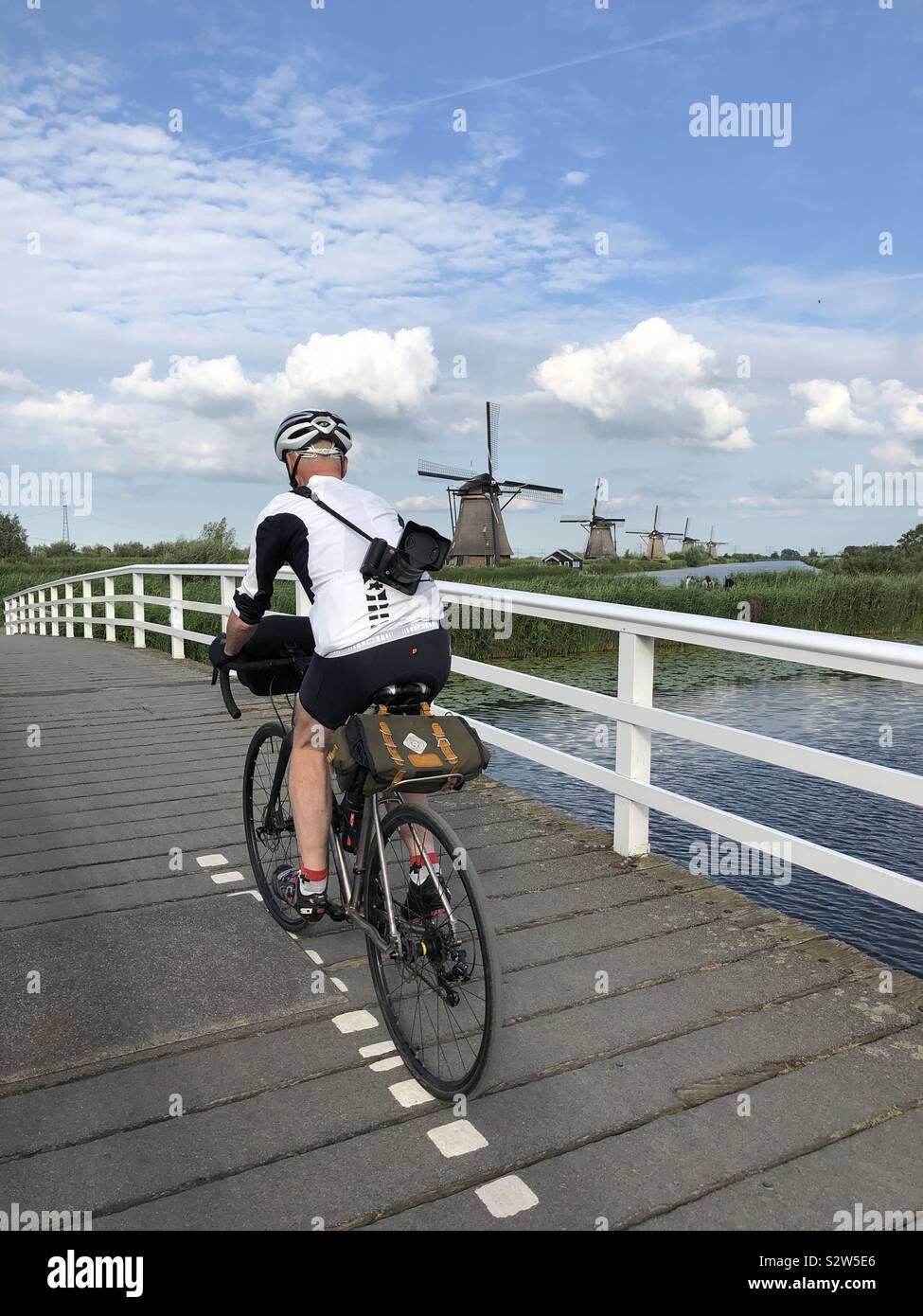 Ciclista maschio a cavallo su ponte a Kinderdijk sito UNESCO, Paesi Bassi. Foto Stock