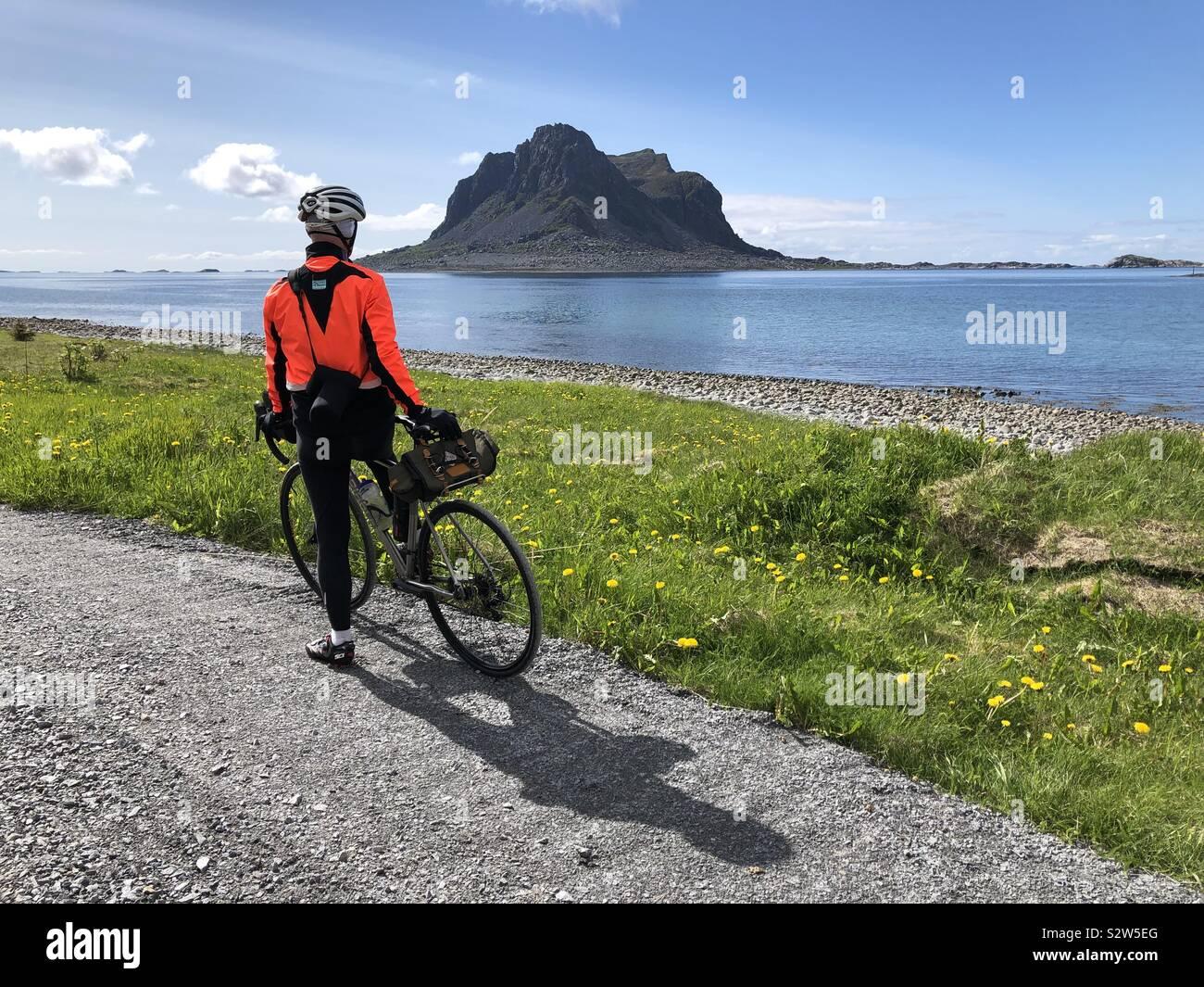 Ciclista guardando fuori dall isola di Vega, Norvegia. Foto Stock