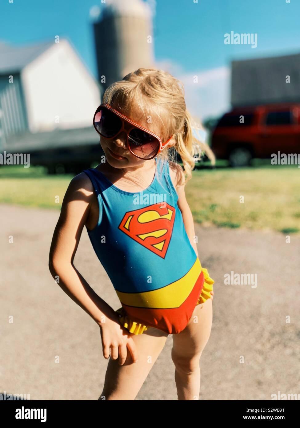 Giovane ragazza in rosso gli occhiali da sole e costume da bagno supergirl in posa con atteggiamento sassy Foto Stock