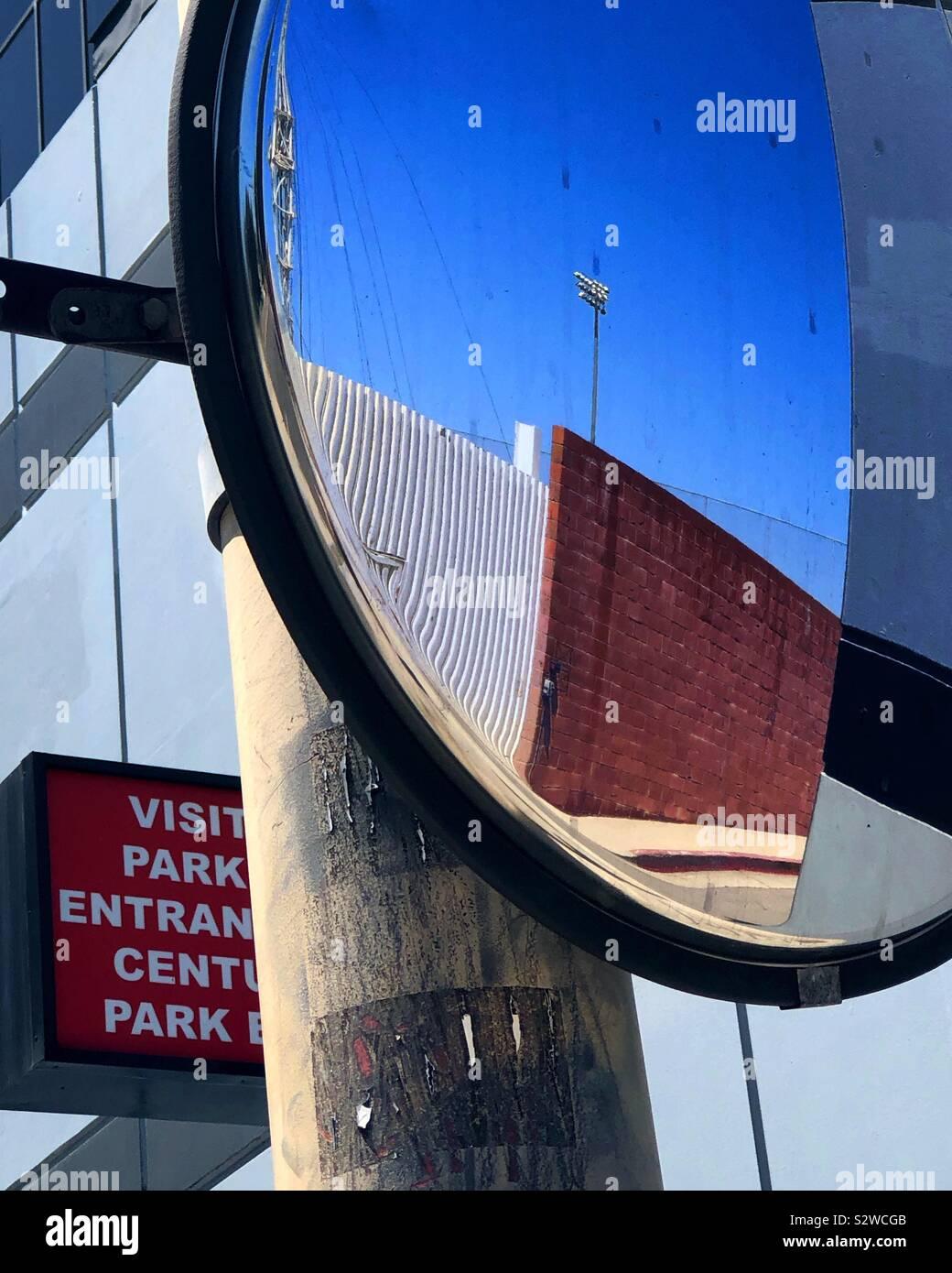 Parcheggio specchio riflette un vuoto di un muro di mattoni in un vicolo e il cielo aperto. Foto Stock