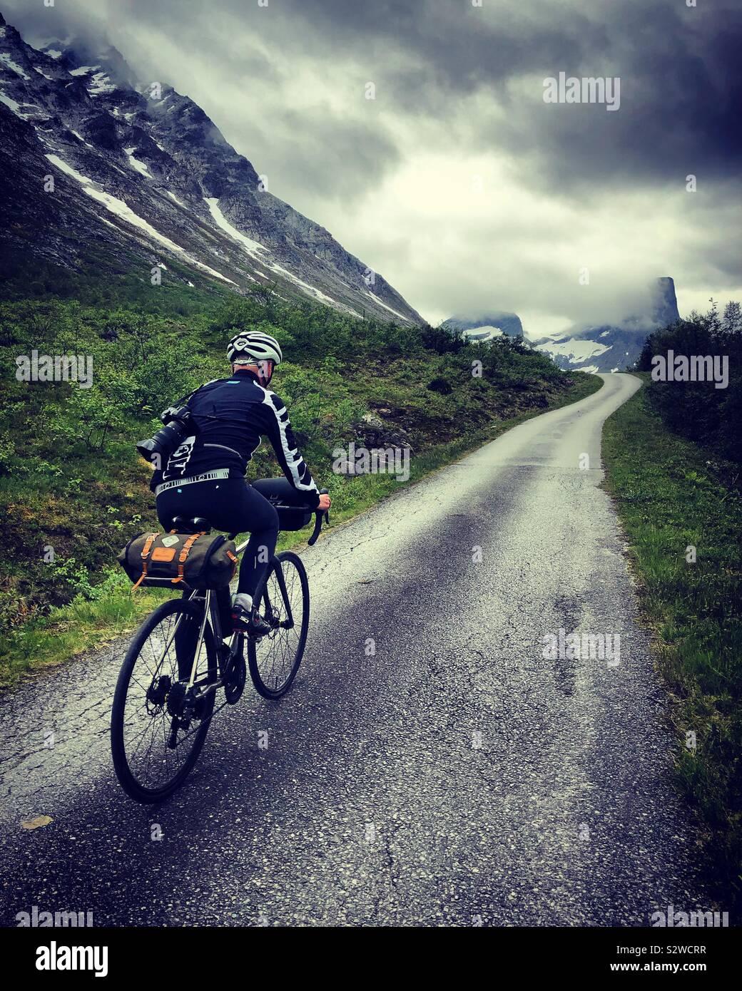Ciclista maschio nella valle Romsdal, Norvegia Foto Stock
