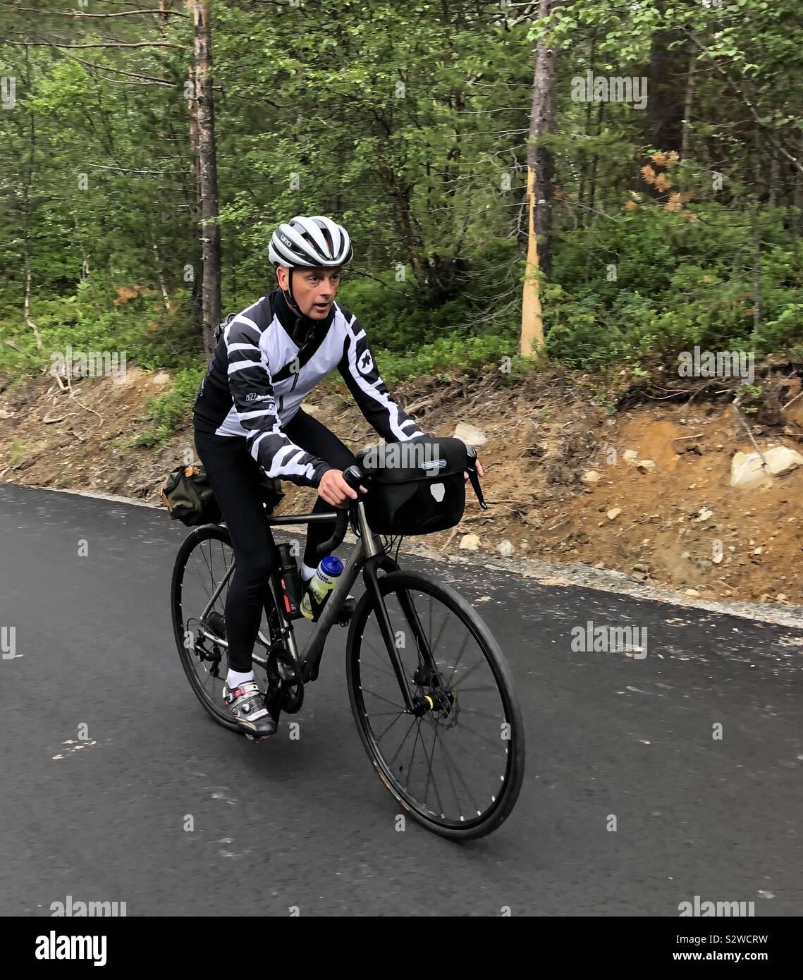 Ciclista maschio salire ripida collina nella valle Romsdal, Norvegia Foto Stock