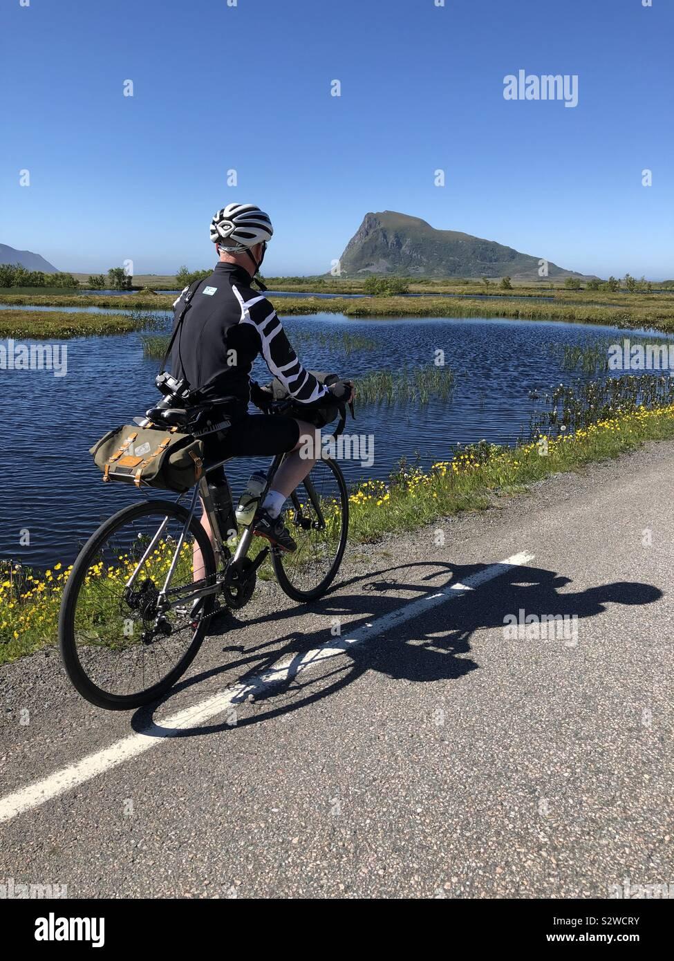 Ciclista maschio vicino Gimsoya, Isole Lofoten in Norvegia. Foto Stock