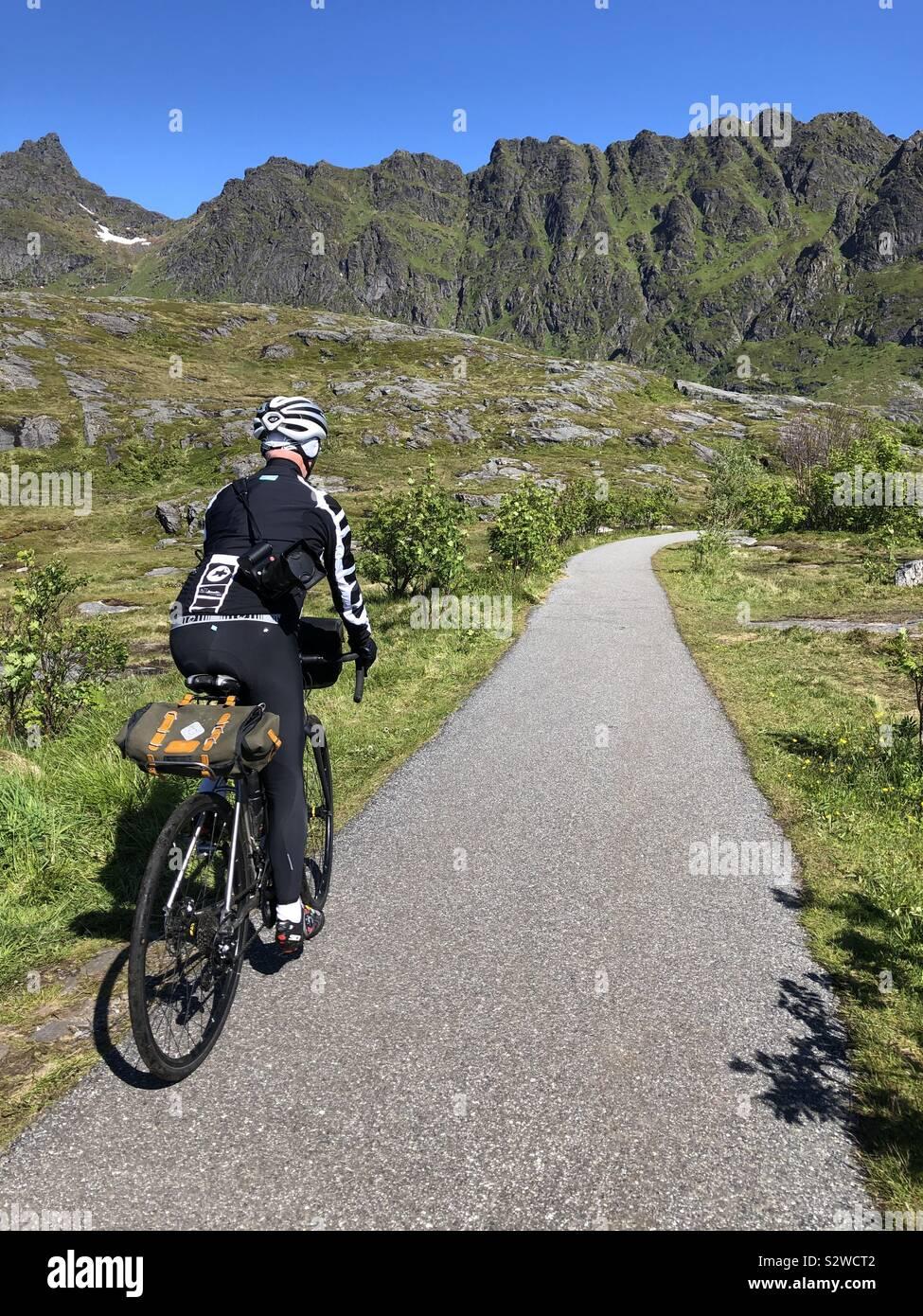Maschio ciclista pedalando attraverso le isole Lofoten in Norvegia. Foto Stock