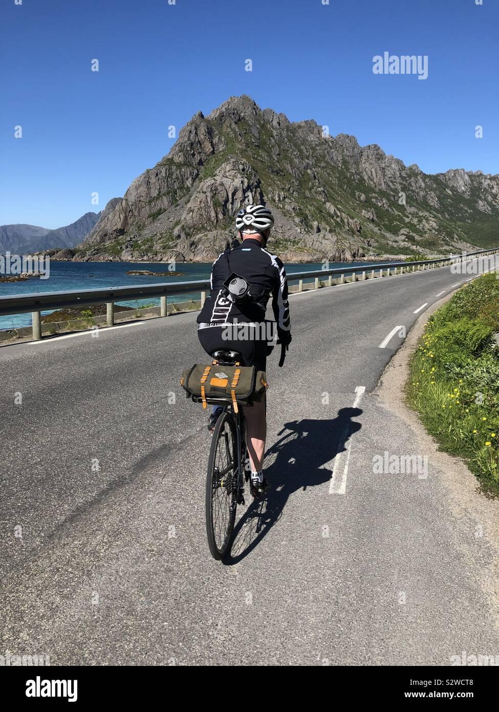 Ciclista maschio a cavallo lungo la strada per Henningsvaer, Isole Lofoten in Norvegia Foto Stock